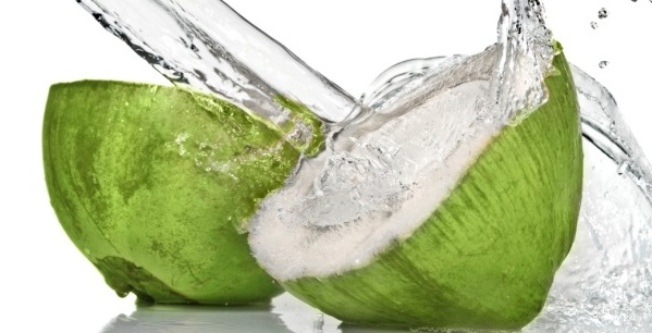fresh cut green coconut with water splash on white