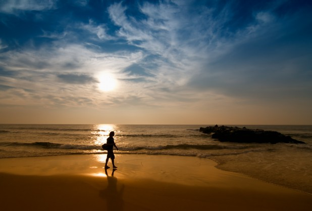 Lone person with fishing rod, as the sun rises on the beach
